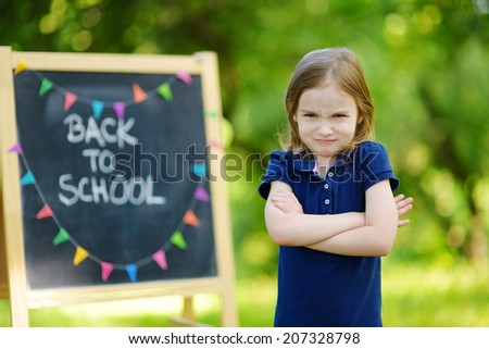 Adorable little schoolgirl feeling unhappy about going back to school - stock photo