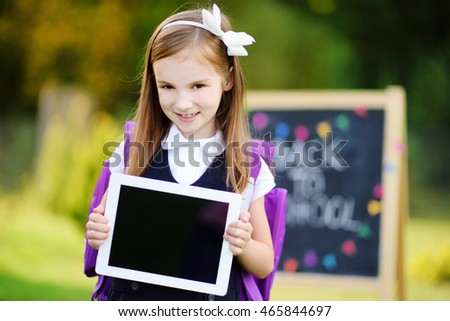 Adorable little schoolgirl holding digital tablet. Back to school concept.