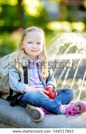 Adorable little schoolgirl in a city park on bright autumn day. Education for young kids. Back to school concept.