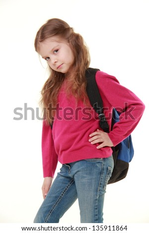 Adorable little schoolgirl in jeans and a sweater holding a school bag on a white background on Education