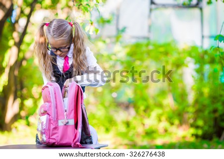 Adorable little schoolgirl with a backpack going back to school outdoor - stock photo