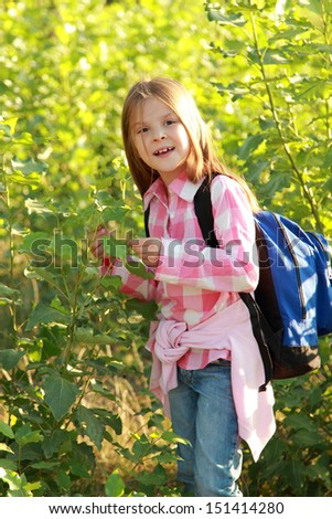 Adorable little schoolgirl with backpack goes to school on Education - stock photo