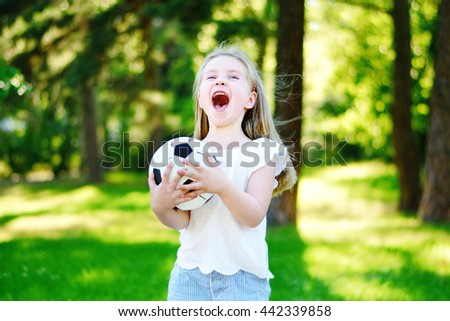 Adorable little soccer fan cheering on hot summer day at park - stock photo