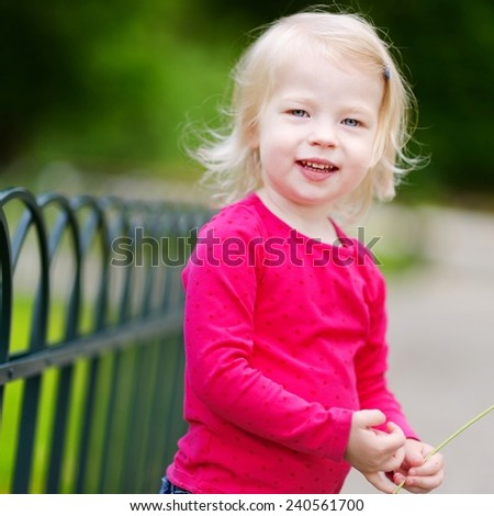 Adorable little toddler girl having fun outdoors on warm summer day - stock photo