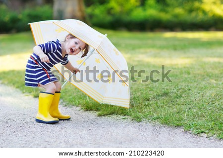 Adorable little toddler girl having fun with umbrella in yellow rain boots and umbrella in summer park. - stock photo