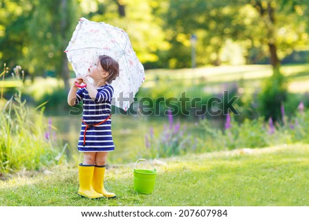 Adorable little toddler girl in yellow rain boots and umbrella in summer park. - stock photo