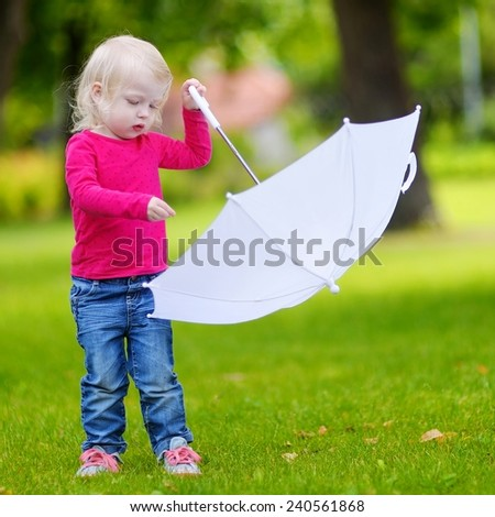 Adorable little toddler girl playing with white umbrella on warm summer day - stock photo
