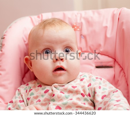 adorable little toddler girl sitting in a high chair - stock photo