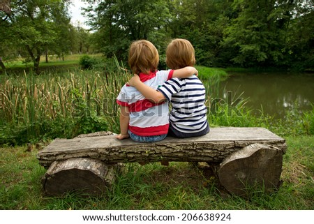 Adorable Little Twin Brothers Sitting on a Wooden Bench, Embracing Each Other and Looking at Beautiful Lake at Summer - stock photo