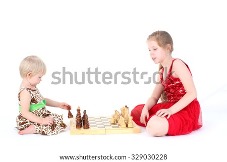 adorable little two sisters 9 year and  1  year old learning play in chess - stock photo