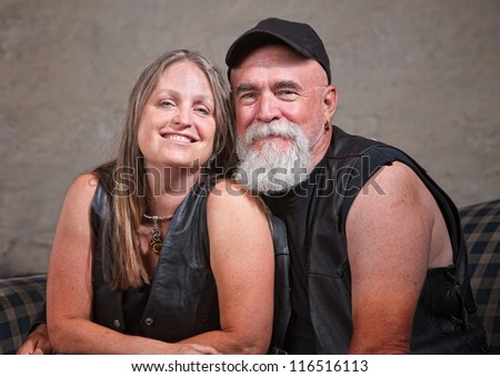Adorable mature biker couple wearing leather vests