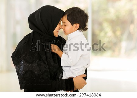 adorable middle eastern woman playing with her son at home - stock photo