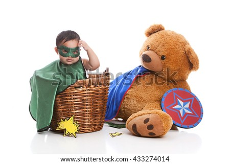 Adorable, mixed race baby boy dressed as a superhero and sitting in a laundry basket next to a large stuffed bear wearing a cape and holding a shield.  Isolated on white. - stock photo