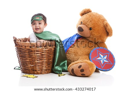 Adorable, mixed race baby boy dressed as a superhero and sitting in a laundry basket next to a large stuffed bear wearing a cape and holding a shield.  Isolated on white.