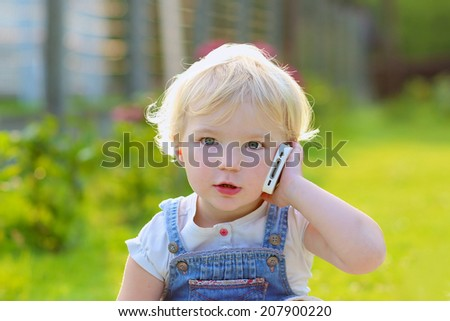 Adorable modern little kid, blonde toddler girl, talking by mobile phone outdoors in natural environment - stock photo