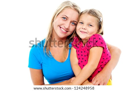 Adorable mom and daughter posing together. Indoor studio shot - stock photo