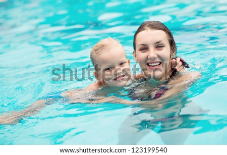 Adorable mom and kid keeping fit and healthy in water - stock photo