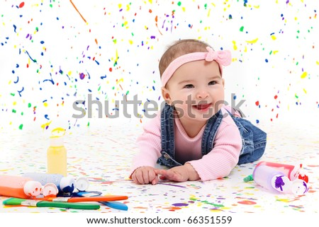 Adorable 4 month old baby girl laying on paint splattered background.