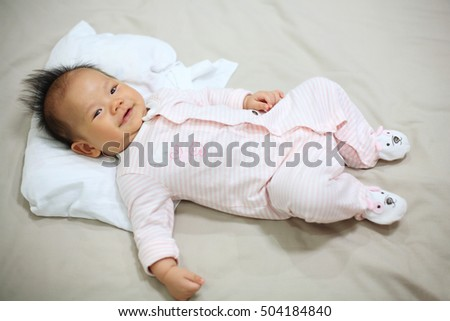 Adorable 3 months old baby boy smile on the bed