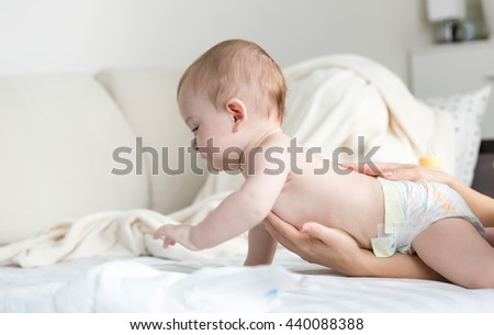 Adorable 9 months old baby in diapers crawling on bed while mother is helping him - stock photo