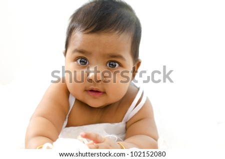 Adorable 6 months old Indian baby girl looking at camera - stock photo