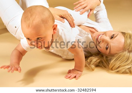 Adorable Mother and Child, playing together on the floor, baby crawling