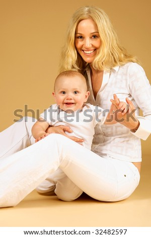 Adorable Mother and Child, playing together, on the ground