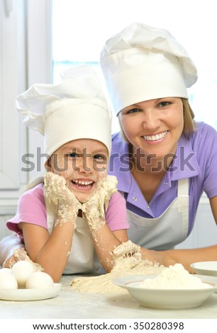 Adorable mother and daughter cooking together in the kitchen - stock photo