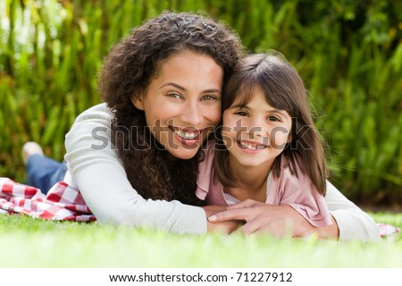 Adorable mother with her daughter in the garden - stock photo
