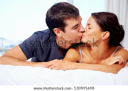 adorable multiracial couple kiss on bed at home lifestyle - stock photo