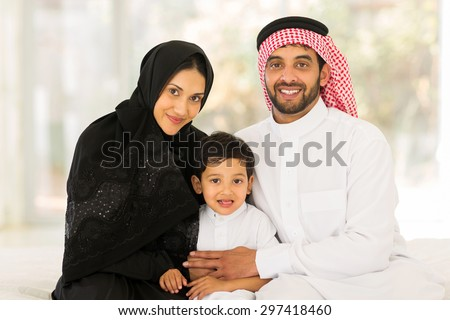 adorable muslim family sitting at home - stock photo