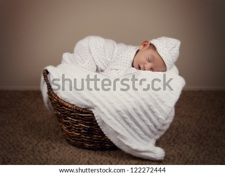 Adorable new baby born child sleeping in pajamas in a wicker - stock photo