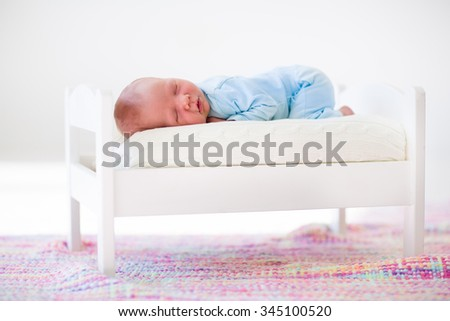 Adorable new born child sleeping in a white toy bed. Nursery for newborn baby. Cute little boy taking a nap in sunny bedroom. Bedding and textile for kids. Family with children. Healthy infant sleep. - stock photo