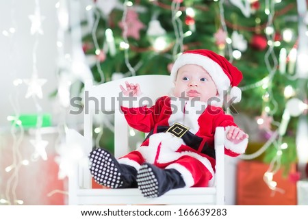 Adorable newborn baby boy in Santa outfit sitting in a white chair next to a beautiful Christmas tree and present boxes