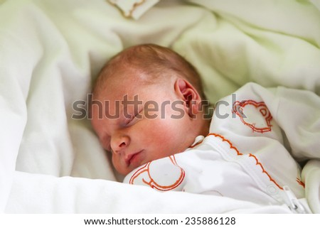 Adorable newborn baby boy on his first day sleeping - stock photo