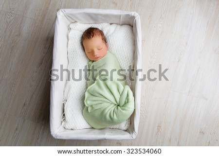 Adorable newborn baby boy sleeping in white basket. Copy space. Horizontal composition. - stock photo