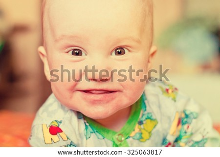 Adorable newborn baby boy smiling portrait. Image with vintage filter