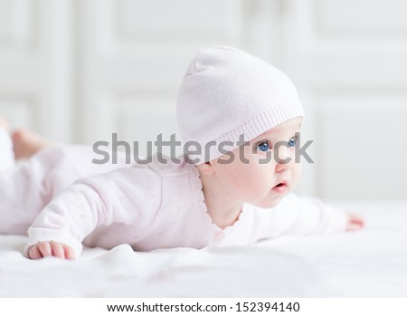 Adorable newborn baby girl in a pink knitted hat playing on her tummy on a white blanket - stock photo
