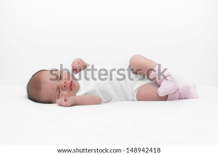 Adorable newborn baby girl is napping on white blanket