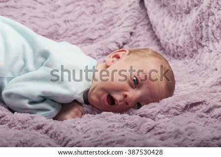 Adorable newborn baby on her side with funny expression - stock photo