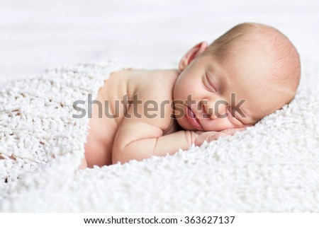 adorable newborn boy sleeps on the white blanket with background