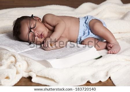 Adorable newborn sound asleep on a big book. - stock photo
