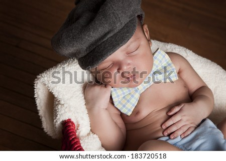 Adorable newborn wearing a bow-tie and hat fast asleep in a red basket. - stock photo
