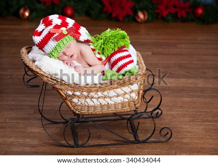 Adorable newborn wearing a red, white and green striped hat and leggings - fast asleep in a little sled.  Christmas decor in the background. - stock photo