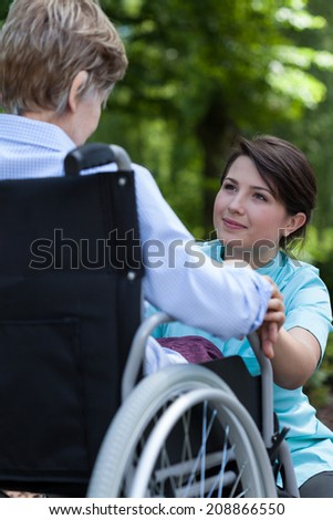 Adorable nurse supports the older a woman with a disability - stock photo