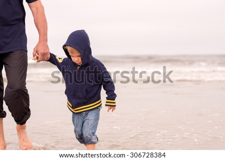 adorable obedient toddler boy walking on a beach holding hands with his father on a cloudy day - stock photo