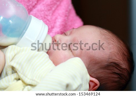 Adorable one month Baby eating from bottle with eyes closed - stock photo