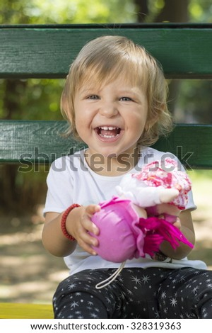 Adorable one year old baby girl with blue eyes sitting on a bench in  a park with a doll in her hands