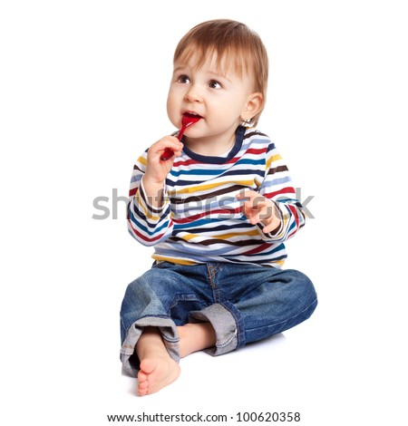 Adorable one year old child biting spoon and smiling, isolated on white.
