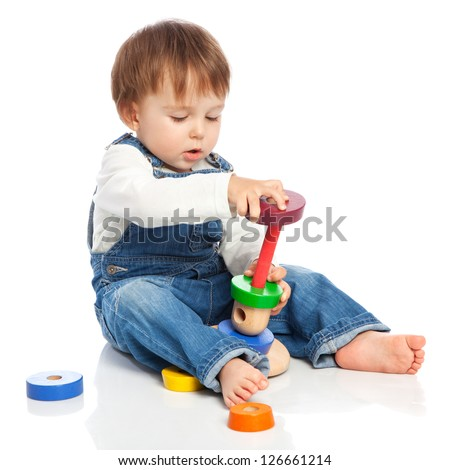 Adorable one year old child playing with colour rings, isolated on white - stock photo